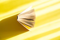 Opened book on a yellow background in the bright sun. The concept of education, reading, buying books. Copy space.  stock photography