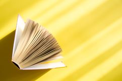 Opened book on a yellow background in the bright sun. The concept of education, reading, buying books. Copy space.  royalty free stock photography