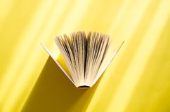 Opened book on a yellow background in the bright sun. The concept of education, reading, buying books. Copy space.  stock image