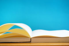 An opened books in blue background. In the image, there are an opened books. They are on a wooden table and they are in the blue background stock photography