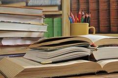 Opened books on a bookshelves background. Three opened books lie one on other on a background of bookshelves stock photo