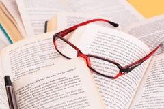 Opened books, eyeglasses and pen Stock Image