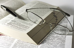 Opened books, glasses and pen Stock Images