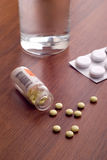 Opened bottle of pills. Pills and glass of water on table Stock Photo