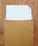 Opened brown envelope with white paper Stock Photos
