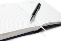 Opened business diary with a pen over white Stock Images