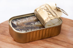 Opened can of sardines on wooden board Royalty Free Stock Image