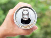 Sparkling water in can. Opened can with sparkling water in hand on green nature background Royalty Free Stock Photography