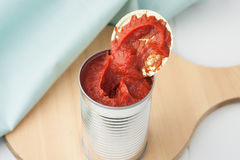 Opened can of tomato paste. On wooden round cutting board Royalty Free Stock Images