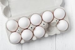 Opened cardboard box of eggs on wooden table. One egg missing stock photos