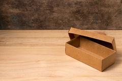 Opened cardboard box on wooden background Stock Images