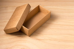 Opened cardboard box on wooden background Stock Photography