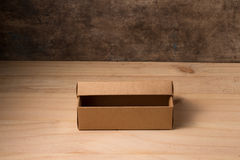 Opened cardboard box on wooden background Royalty Free Stock Photos