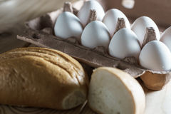 Opened cardboard egg box with white eggs and bread on a wooden background. White eggs on wooden background Royalty Free Stock Photos