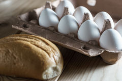 Opened cardboard egg box with white eggs and bread on a wooden background. Stock Photos