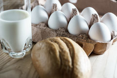 Opened cardboard egg box with white eggs, milk and bread on a wooden background. White eggs on wooden background Royalty Free Stock Image