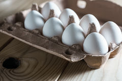 Opened cardboard egg box with white eggs on a wooden background. White eggs on wooden background Royalty Free Stock Photo