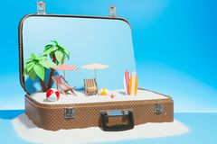 Opened case with beach model in studio. Small fake beach with chaise-longue surfboard and palms in baggage on blue background stock photos
