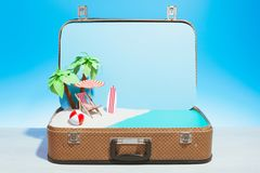 Opened case with beach model in studio. Small fake beach with chaise-longue surfboard and palms in baggage on blue background royalty free stock image
