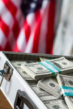 Opened case with dollar bundles. Cash near american flag. Freedom and opportunities. Richness and glory stock image