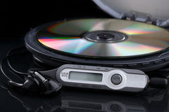 Opened CD audio player with disc inside on black background. Opened personal cd player with remote control and portable audio earphones on black background stock images