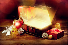 Opened chest with light, gift and other christmas decoration on old wooden table. Retro style with old textured paper Royalty Free Stock Photos