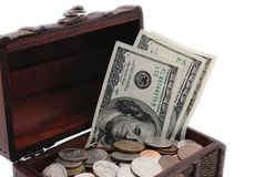 Opened chest with US coins and dollar bills in it. Stock Photos
