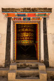 Opened colorful door with buddhist praying instrument inside the room with ancient scripts on it Royalty Free Stock Image