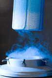 Opened container with liquid. Nitrogen, blue light and vapour Stock Images