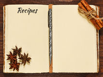 Opened cookbook and spices. Opened blank old cooking book on the wooden table with cinnamon and anise royalty free stock photography