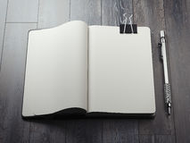 Opened copybook with black clip and silver pen. 3d rendering Stock Images
