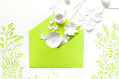 Opened craft paper envelope full of spring blossom sakura paper flowers on white background. Royalty Free Stock Photos
