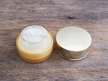 Opened cream container and cap Royalty Free Stock Image