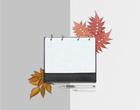 Opened day planner with red autumnal leaves and pencil, pen on different grey light background. Flat lay. Workspace with checkered Royalty Free Stock Photography