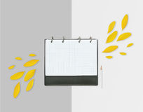 Opened day planner with yellow petals and pencil on grey background. Flat lay. Workspace with checkered sheet, place for text Royalty Free Stock Photo