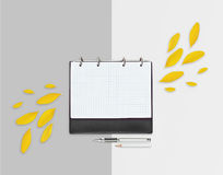 Opened day planner with yellow petals and pencil, pen on grey background. Flat lay. Workspace with checkered sheet, place for text Royalty Free Stock Images