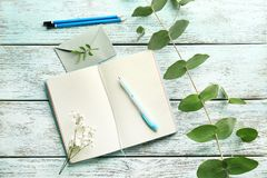 Opened diary and flowers. On wooden table stock image