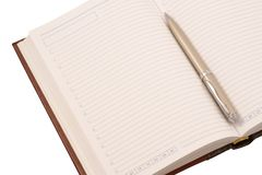 Opened diary and pen (isolated). Close up of opened diary and pen on white background Royalty Free Stock Image