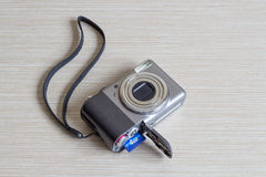 Opened digital photo camera. Photo camera at white wooden background Royalty Free Stock Image