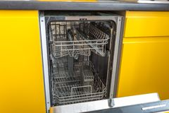 Opened dishwasher in the yellow kitchen royalty free stock photos