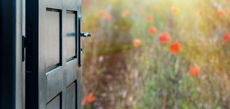 Opened door concept to beautiful and imaginary poppies field stock photos