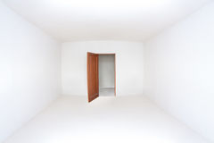 Opened door in the empty white room Royalty Free Stock Image