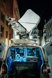 Opened door of parked satellite TV van transmitting breaking new. S events to satellites for broadcast around the world at night in city Stock Photos