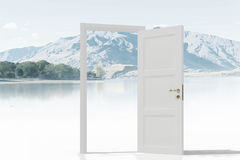 Opened door to somewhere. Home white opened door against natural landscape Stock Photos