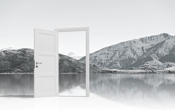 Opened door to somewhere. Home white opened door against natural landscape Royalty Free Stock Image
