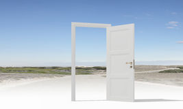 Opened door to somewhere. Home white door open in cloudy sky Stock Image
