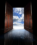 Opened doors. Two old wooden doors open from a dark room to reveal an bright blue sky and stars.  Concept for new beginnings or adventure into the future