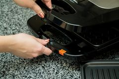 Opened Electronic Waffle maker with a women hand. Sample model for Kitchen appliance. Electronic Waffle maker. Sample model for Kitchen appliance stock photography