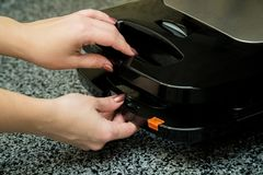 Opened Electronic Waffle maker with a women hand. Sample model for Kitchen appliance. Electronic Waffle maker. Sample model for Kitchen appliance stock images