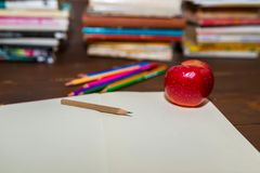 Opened empty notebook, apple, color pencils, colorful books in the background. Focus on the tip of the pencil royalty free stock photo